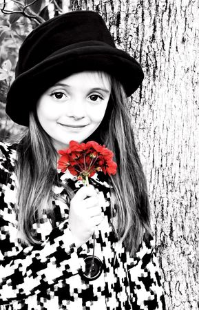 Little girl dressed in a hat and coat holding a red flower