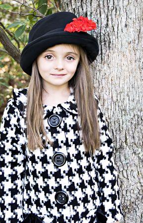 Klein meisje draagt een jas en een hoed met een rode bloem Stockfoto