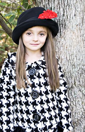 Little girl wearing a coat and a hat with a red flower Stock Photo