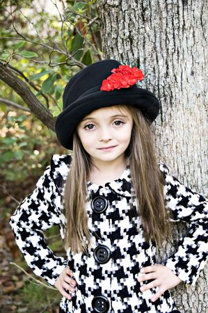Little girl dressed with a coat and hat in an outdoor setting.