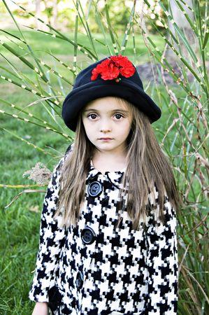 Kleine meisje buitenshuis gekleed in een jas en een hoed.