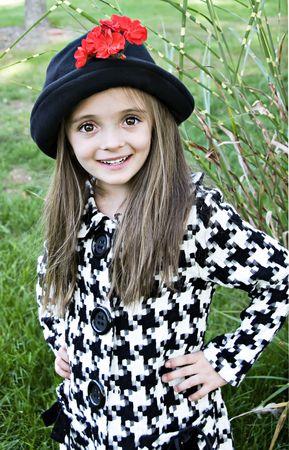 Schattig meisje met een grote glimlach een jas en een hoed te dragen.