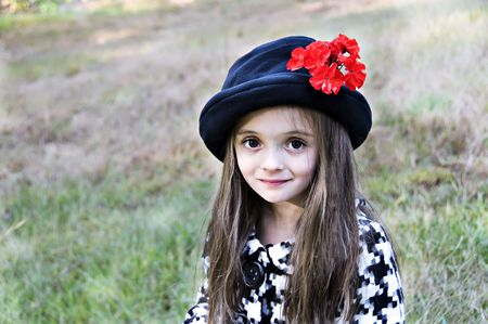 Brown eyed girl wearing a hat with a flower