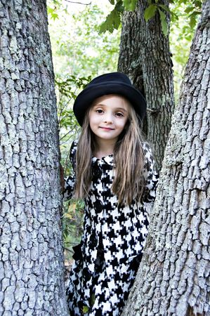 Beautiful little girl wearing a hat and coat standing in a tree. Stock Photo