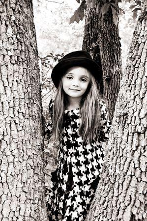 Mooi klein meisje draagt een hoed en jas staat in een boom.