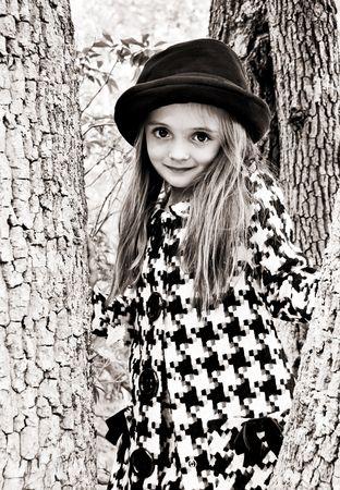 Jong meisje, gekleed in een jas en hoed staat in een boom. Stockfoto