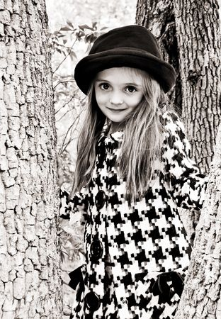 Young girl dressed in a coat and hat standing in a tree.