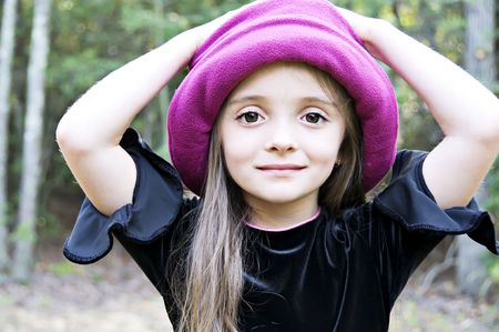 Little girl wearing a hat with hands on her head Stock Photo