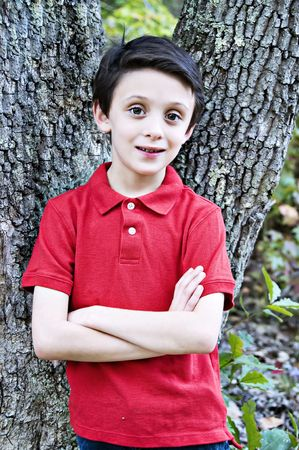 Boy leaning against a tree with his arms crossed.