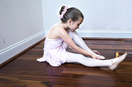 Little girl stretching before ballet class