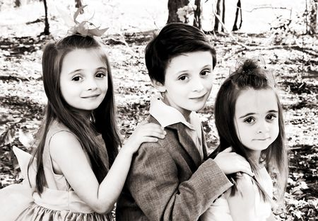 3 children posing for a portrait outdoors. Stock Photo