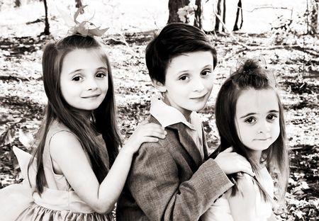 3 kinderen poseren voor een portret buitenshuis.