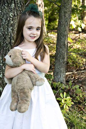 well loved: Shy little girl holding her well loved bear.