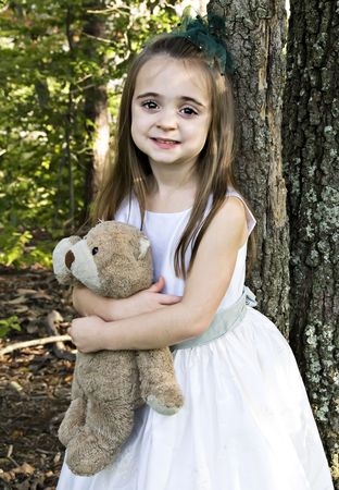 face in tree bark: Girl holding her favorite bear and friend Stock Photo