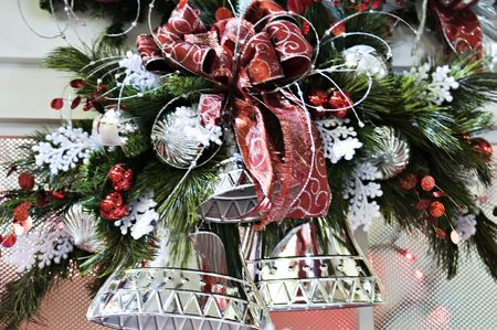 A christmas decoration with silver bells and red bows