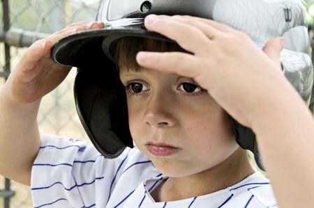 Little boy holding his batting helmet on his head.