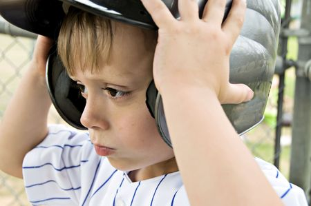 Little boy putting on his batting helmet.