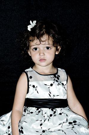 Little curly haired gril poseren voor haar portret. Stockfoto