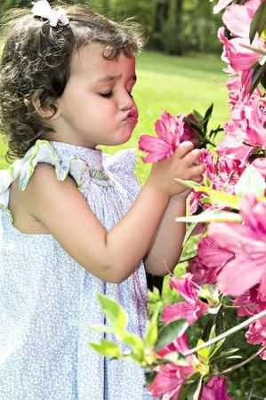 Meisje met haar lippen gebobbeld ruiken van een azalea.