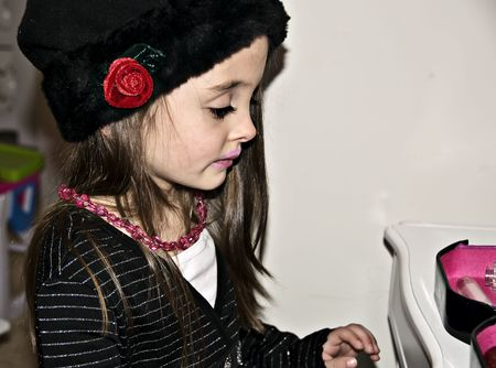 Little girl playing dress up with a hat, beads and make-up
