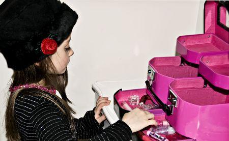Klein meisje dragen van een hoed, kralen en lippen stift afspelen van dress-up.