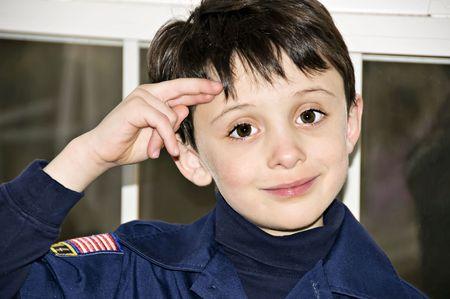 Cute young boy saluting wearing blue