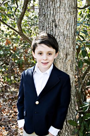 Handsome young brunette boy dressed up wearing a sport coat. Фото со стока