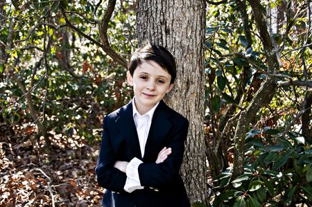 Handsome young boy dressed in a white shirt and Blue Sport coat in an outdoor setting. Stock Photo