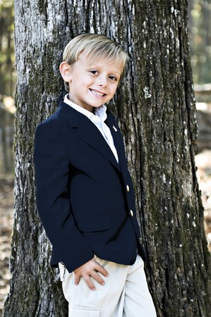 Jonge jongen leunend op een boom met grote bruine ogen en een grote glimlach