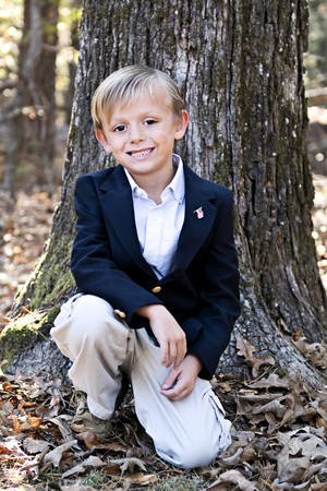 Handsome young boy posing for photo outdoors.