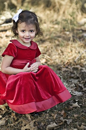 Little girl dressed in red sitting outdoors. Stock Photo