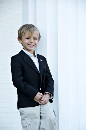 Young boy standing tall next to a column