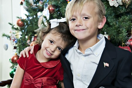 Young boy and girl posing by the Christmas Tree Stock Photo