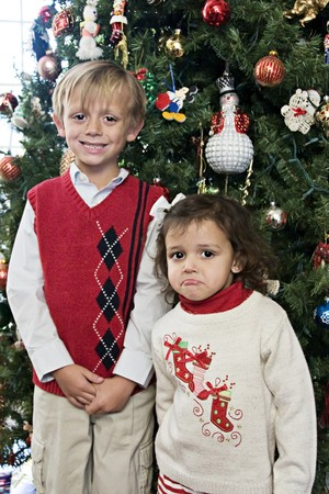 Happy boy and a pouting girl posing for Christmas Stock Photo
