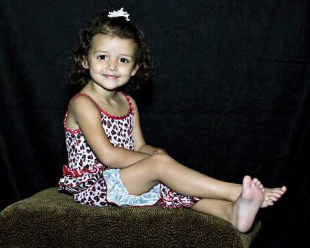 Little girl posing for portrait with curly hair