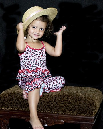 Little girl showing off her straw hat