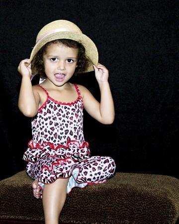小さな女の子のポーズと彼女の麦わら帽子を保持