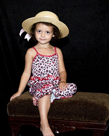 Little girl sitting on a bench wearing a straw hat