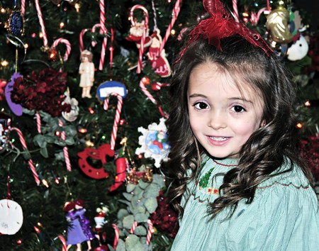Little girl by the Christmas tree in holiday clothing. Stock Photo