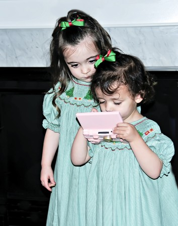 Two little girls playing a video game at Christmas with great intensity.