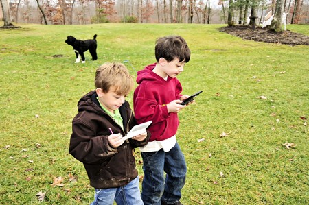 Two boys intensely  playing Video games outdoors  Stock Photo