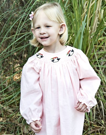 Little blue eyed girl outdoors dressed in a pink dress