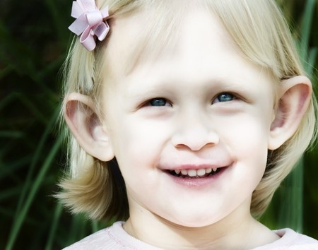 Cute little blonde girl close-up with a big smile.