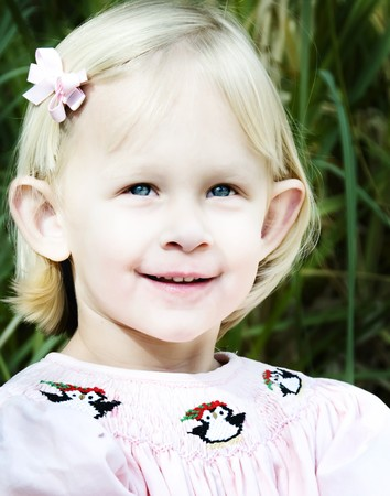 Little blonde, blue-eyed girl wearing a pink hairbow.