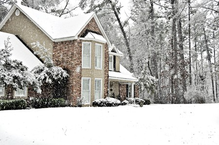 Executive home covered with a white snow blanket on a cold winter day.