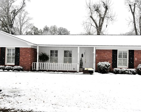 A ranch house covered with falling snow.