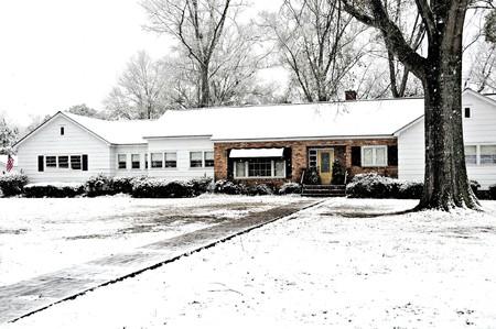 農場の家は誇らしげにアメリカ国旗を飛んで雪で覆われています。