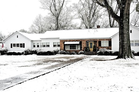 A farm house covered with snow proudly flying an american flag.
