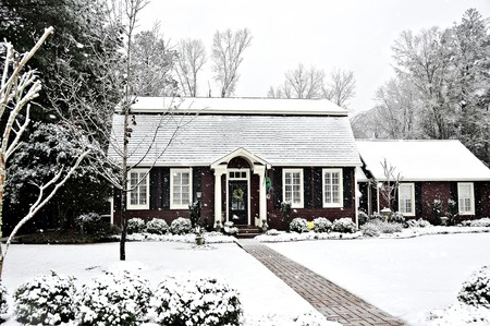 A salt box style home covered with fresh snow. photo