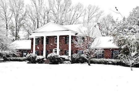 エグゼクティブれんが造りの家美しい新しい雪で美しく飾られて。